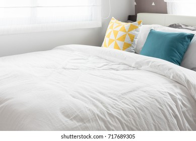 colorful pillows on white bed in modern bedroom, interior design concept
