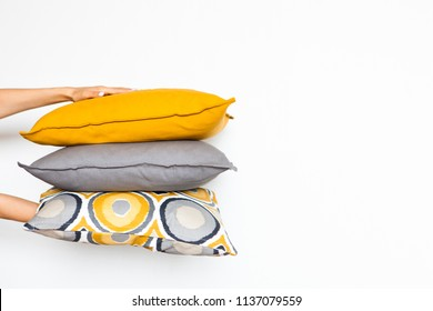 Colorful pillows in women's hands on a white isolated background, the concept of home comfort