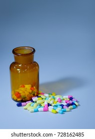 Colorful pills and bottle on table