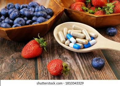 Colorful pills and capsules with fresh fruits and vegetables. Vitamins and supplement from fruits concept