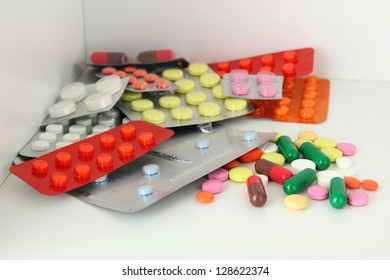 Colorful pills and capsules on shelf