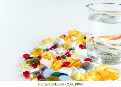 Colorful pills and glass of water, on white background