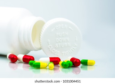 Colorful pills on white background and plastic bottle with blank label and copy space. Childproof packaging. Child resistant pill container. Push down and turn cap.Global healthcare concept.
