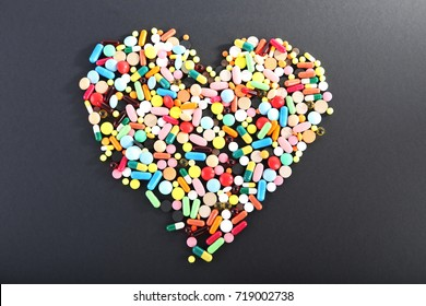 Colorful pills in shape of heart on black background