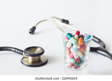 Colorful pills in small glass on white background.