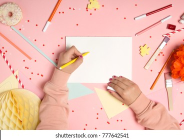 Colorful pink background with party confetti, paper decoration, flags, stationary, children's hands writing on empty card mock-up. Flat lay top view. Learning to draw, making wish list or plans.