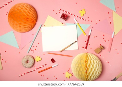 Colorful pink background with party confetti, paper decoration, flags, stationary, DIY supplies, art accessories, brushes and stamp with paper card mock-up. Flat lay top view. Art education concept