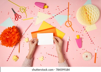 Colorful pink background with party confetti, paper decoration, flags, stationary with woman's hands holding greeting card from envelope. Flat lay top view. Making wish, sending letter invitation