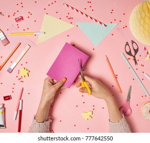 Colorful pink background with various party confetti, paper decoration, flags, stationary, DIY accessories with woman's hands cutting paper card. Handmade concept flat lay top view. Party arrangement