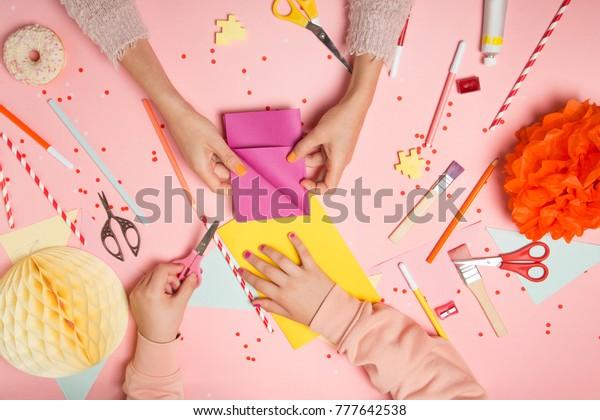 Kleurrijke roze achtergrond met diverse feestconfetti, papieren decoratie, vlaggen, stationaire, doe-het-zelf accessoires met vrouwen- en kinderhanden maken wenskaart. Vet lag bovenaanzicht. Partij-regeling