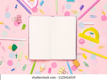 Colorful pink background with various School accessories are laid out in the form of a rainbow. Empty notebook. Flat lay top view. Study arrangement, making wish list or plans.