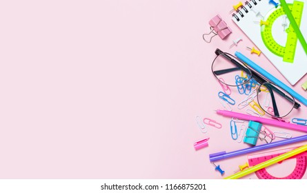 Colorful pink background with various School accessories are laid out in the form of a rainbow. Line, raw. Frame with empty space in center. Flat lay top view. Study arrangement