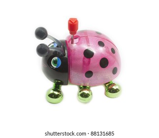 A colorful pink, black, and green toy wind up ladybug ready to be played with.