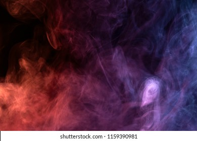 Colorful pink, blue  and red smoke  on a black isolated background. Background from the smoke of vape