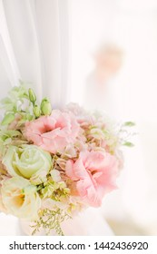 Colorful pink and light green floral arrangement tied to an arch in a wedding ceremony