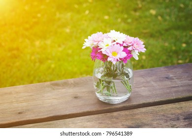 Colorful pink summer flowers in a glass vase outdoors on a rustic wooden garden table with copy space over green grass with golden glow from the sun