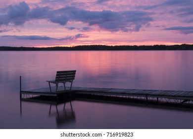 Colorful pink sunset reflected in the calm waters of a Northern Wisconsin lake, with a pier boat dock and a bench. Concepts of tranquility, lake life, resort, tourism and vacation