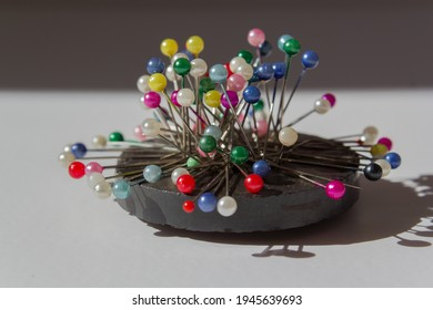 colorful pins on ring magnet white background, magnetic pin needle cushion, tailor, sewing, fashion, design materials equipments, tools, diy, cloth fastening fabric, glass headed pin