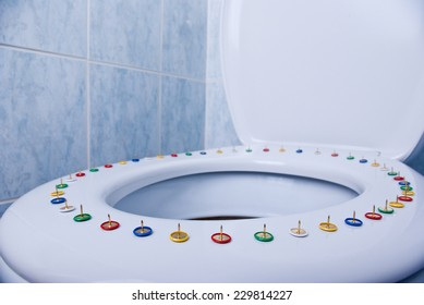Colorful pins on a toilet seat