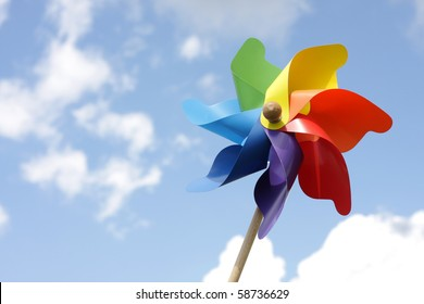 Colorful pinwheel against blue  sky with clouds