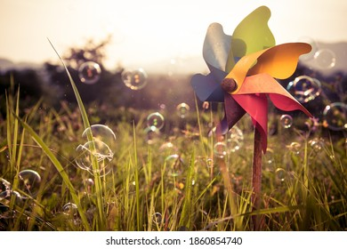 Colorful pinwheel with blowing bubbles in a green field with sunset in the background