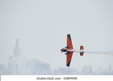 Colorful plane in the sky with a trail of smoke following it and with New York City skyline in the background
