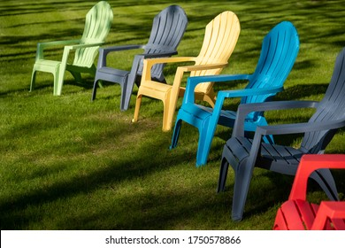 Colorful plastic Adirondack chairs lined up on the grass of a yard in sunlight and shadows on a summer day.