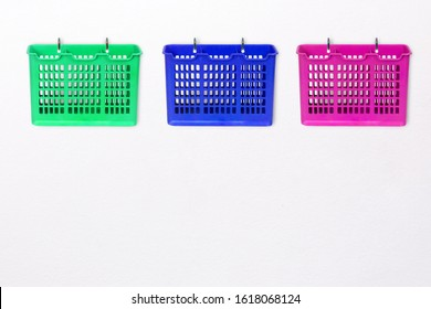 Colorful plastic basket Hanging on white wall background.