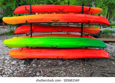 Colorful plastic boats on a rack ashore