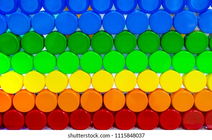 Colorful plastic bottle cap arrange with beautiful tone and pattern. Blue, green, yellow, orange, and red plastic bottle cap arrange with orderly. Cap for bottle of water, and other drink. Cap closure