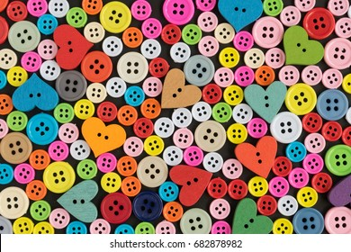 Colorful plastic buttons and wood buttons arranged for background.