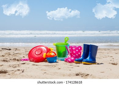 Colorful plastic children's toys on the beach with sea and clouds in background