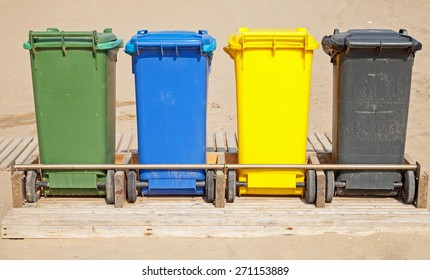 Colorful plastic containers in a row for separate garbage collection, front view