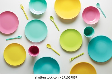 Colorful plastic dishes on white background overlook shot