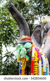 colorful plastic flower garland on elephant statues's neck at Buddhist temple, Believe in Buddhism.