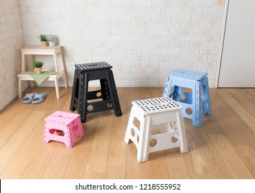 Colorful plastic folding step chair. Over light background. Cozy interior design.