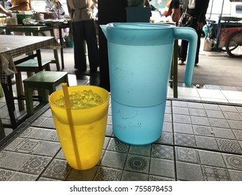 Colorful plastic glass and pitcher on the wooden table - local traditional market/shop enviornment background