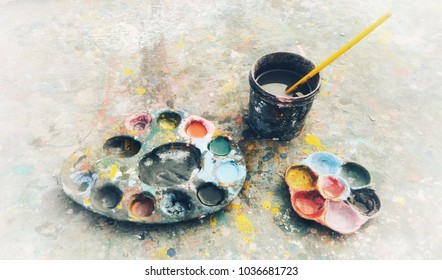 Colorful in plastic palette with watercolor paint on wooden background.
