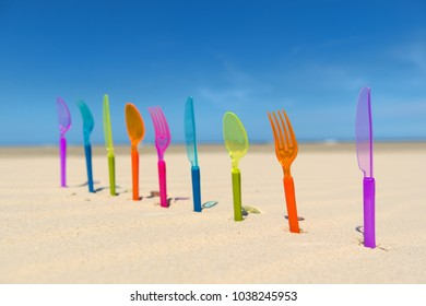Colorful plastic silverware standing in sand at the beach