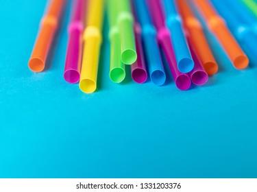 Colorful plastic single use straws on blue background
