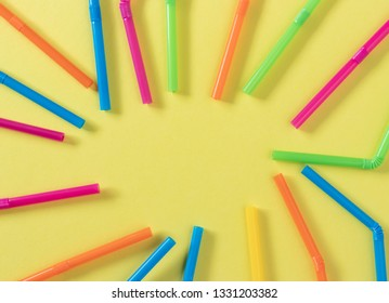 Colorful plastic single-use straws pointing to the center of a yellow flat lay