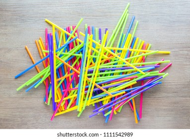 colorful plastic straws in a haphazard pile on a brown wooden table