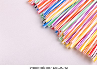 Colorful plastic straws on light background. Event and party supplies. Earth pollution concept
