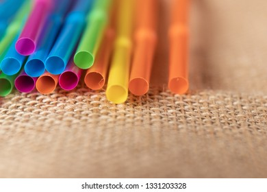Colorful plastic straws on a natural brown fabric