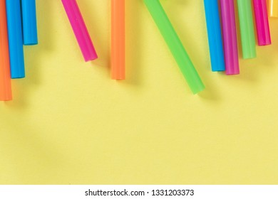 Colorful plastic straws on pastel yellow flat lay background