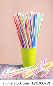 Colorful plastic straws in paper cup on wooden background. Event and party supplies. Earth pollution concept