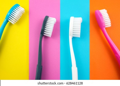 Colorful Plastic Toothbrushes on Paper Colors Background.