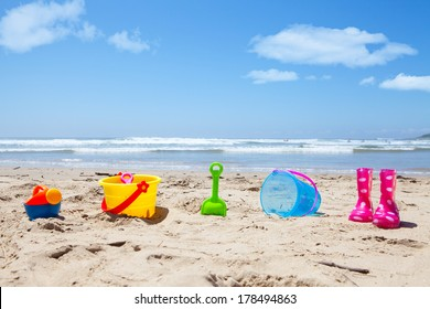 Colorful plastic toys and gumboots on beach sand with sea in background