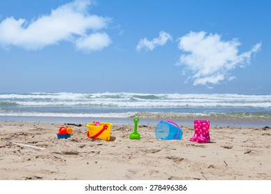 Colorful plastic toys lying on the beach sand with the sea and clouds in the background