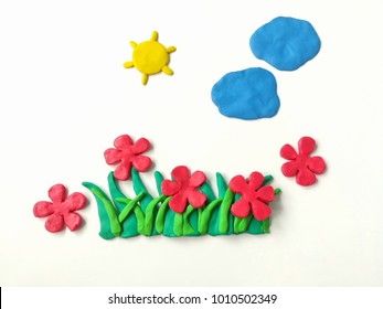 Colorful plasticine clay dough made are red flowers grass sun and clouds on white background, beautiful nature